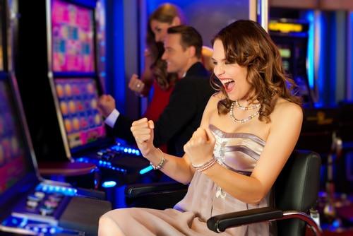 Jeune femme gagnant à la machine a sous