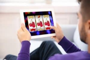 Homme jouant a la machine a sous sur tablette - Casinosansdepot.net