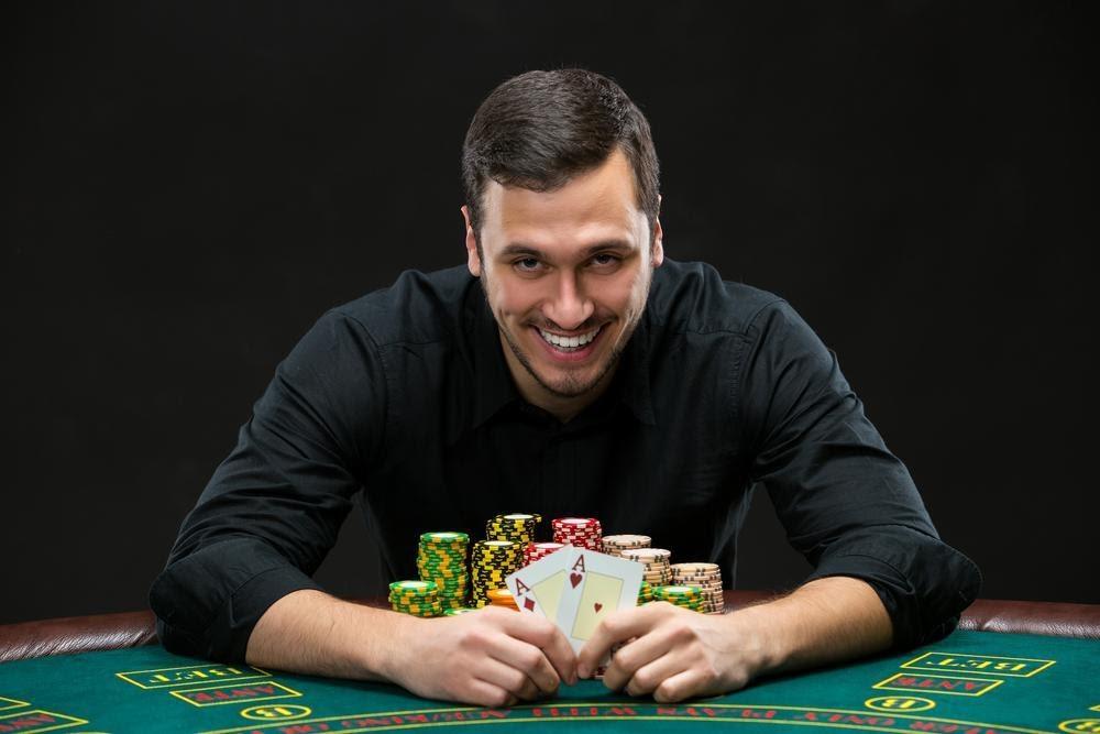 joueur souriant avec paire d'as en main et piles de jetons