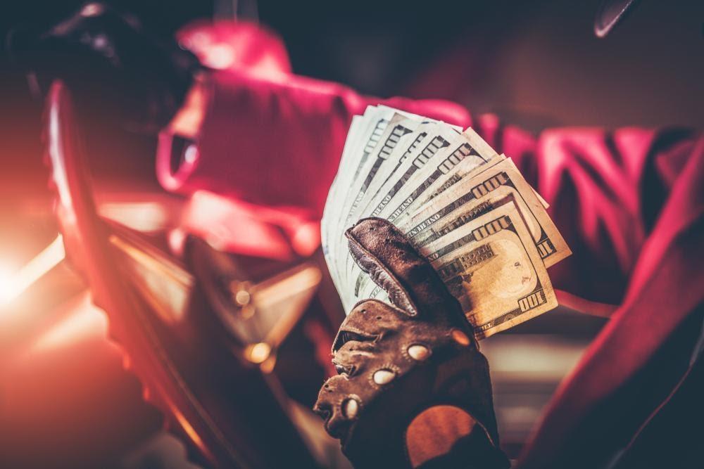 casino drive-in homme montrant des billets de 10 dollars